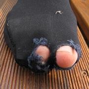 Ein Strumpf mit zwei Löchern, aus denen Zehen hervorluken.