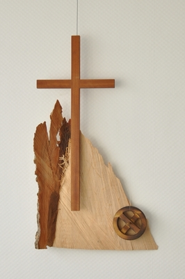 Ein Holzkreuz vor einem Holzbrett und einem kleinen Rad aus Holz