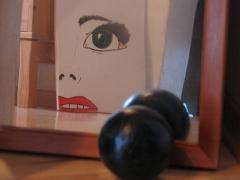 Ein gemaltes Bild im Spiegel. Auf dem Bild ist eine Gesichtshälfte zu sehen