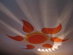Eine beleuchtete an eine Wand stilisiert gemalte Sonne