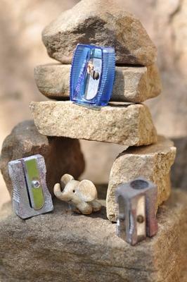 Übereinandergeschichtete Steine. Darauf liegen drei Anspitzer. Außerdem steht darauf ein kleiner, aus ton modellierter Elefant.