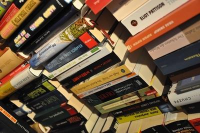Viele Bücher zu mehreren Stapeln getürmt.