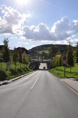 Eine Straße führt einen Berg herunter, weiter unten führt eine Brücke über die Straße.