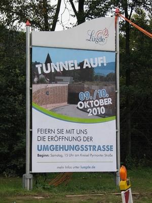 Eine große Stellwand mit einem Plakat zur Eröffnung der Umgehungsstraße Lügde.