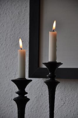 Zwei Kerzenständer mit zwei brennenden Kerzen.