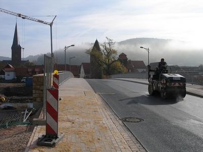 Eine frisch asphaltierte Brücke wird mit einer Walze planiert.