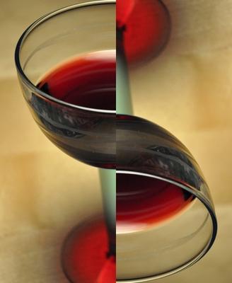 Foto von einem gefülltem Rotweinglas, in der Mitte geteilt, eine Hälfte gedreht und wieder zusammengefügt.