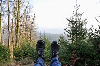 Eine Landschaftsaufnahme mit Bergen, im Vordergrund Schuhe.