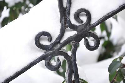 Ein verschnörkeltes Detail von einem Treppengeländer, darauf liegt Schnee.