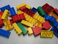 Legosteine liegen verstreut auf einer Tischplatte