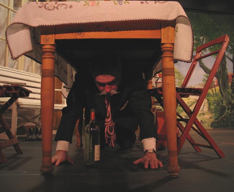 """Eine Szene aus dem Stück """"Kohle, Moos und Mäuse"""", gespielt von der Elbrinxer Dorfbühne. Richard Reichmacher ein Inspektor der Lotteriegesellschaft versteckt sich unter einem Tisch."""
