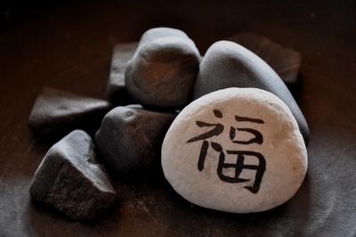 Foto: Mehrere schwarze Steine, ein weißer Stein mit einem schwarzen Schriftzeichen
