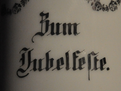 """Bildausschnitt von einem Milchkännchen. Darauf der Schriftzug """"Zum Jubelfeste"""""""