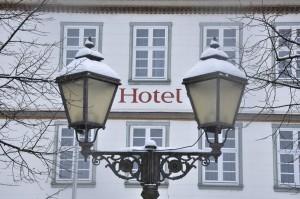 Zwei Straßenlaternen, im Hintergrund ein Gebäude, darauf ist das Wort Hotel zu lesen.