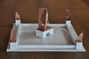 Brunnenmodell: In einer Art Scherenschnitt sind vier skizzierte Szenen mit Ziegen um einen Brunnen angeordnet.