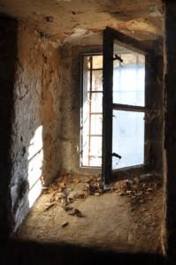 Ein halboffenes Fenster, davor ein Gitter.
