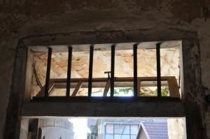 Ein geöffnetes Oberlichtfenster einer Eingangstür, davor ein Gitter.