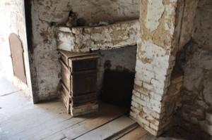 Ein alter Eisenofen vor altem Mauerwerk.