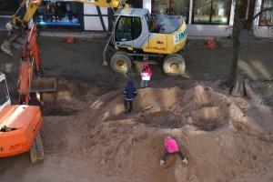 Ein großer Sandhaufen, darin spielen drei Kinder, neben dem Sandhaufen stehen zwei Bagger.