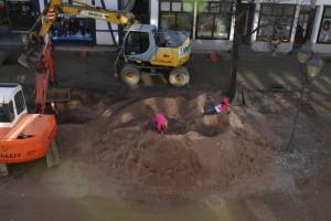 Zwei Kinder spielen in einem großen Sandhaufen, neben dem Sandhaufen stehen zwei Bagger.