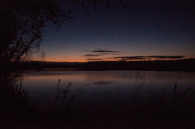 Ein See, im Hintergrund das letzte rötliche Licht der untergehenden Sonne.