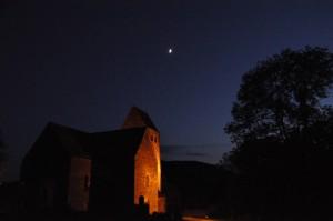 Eine beleuchtete Kirche bei Nacht, darüber ein Mond.