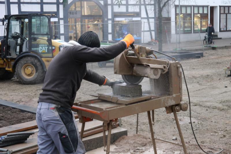 Ein Mann sägt mit einer Steinsäge in einen Pflasterstein.