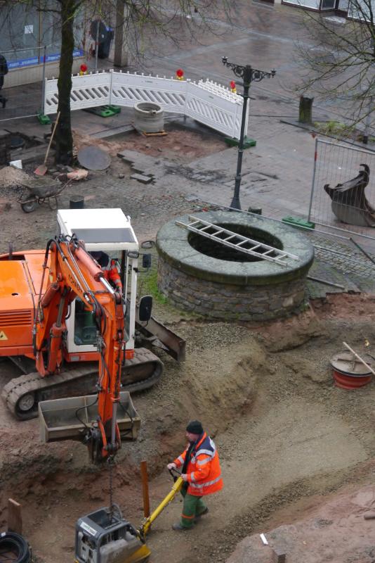 Ein Brunnen, ringsherum Baugeräte im Einsatz.