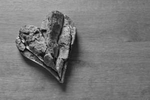 Ein Herz aus Holz liegt auf einem Holztisch.