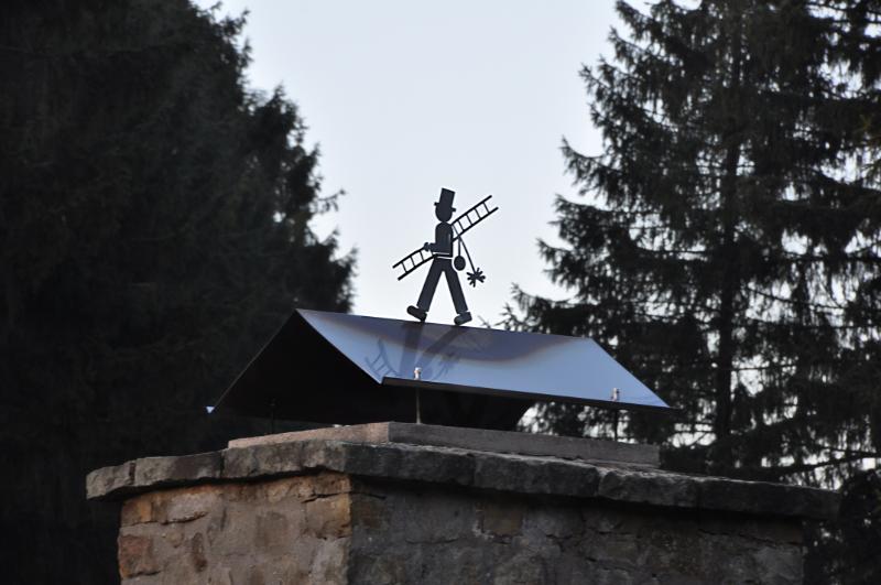 Eine kleine Plastik in Form eines Schornsteinfegers auf dem Schornstein von einer Schutzhütte.