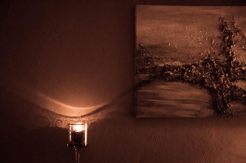Das Schattenspiel einer Kerze an einer Wand scheint ein an der Wand hängendes Kunstwerk zu ergänzen.