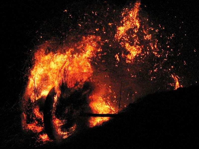 Ein Holzrad rollt einen Berg hinunter. Das zwischen den Speichen gestopfte Roggenstroh brennt
