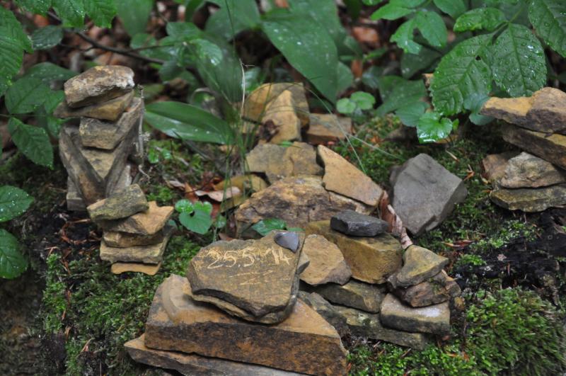 Mehrere Kreationen aus kleinen Steinen. Auf einem Stein ist das Datum 25.5.14 eingeritzt.