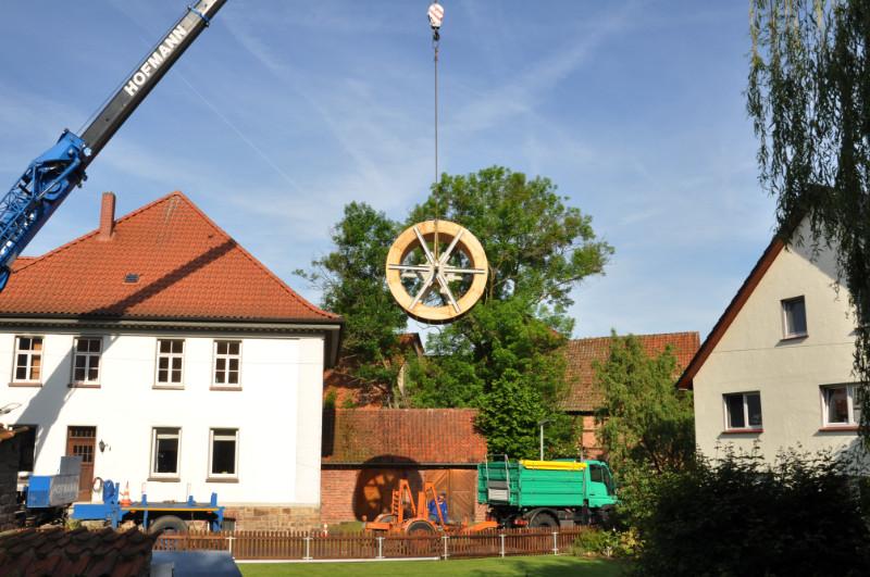 Das neue Elbrinxer Mühlrad hängt an den Seilen eines großen Kranwagens