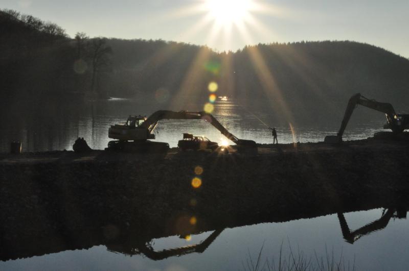 Zwei Bagger stehen am Schiedersee. Dazwischen ein Angler der seineAngelrute auswirft. Im Hintergrund geht die Sonneunter.