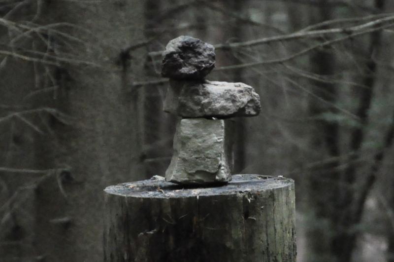 Drei Steine sind auf einem Baumstumpf gestapelt.