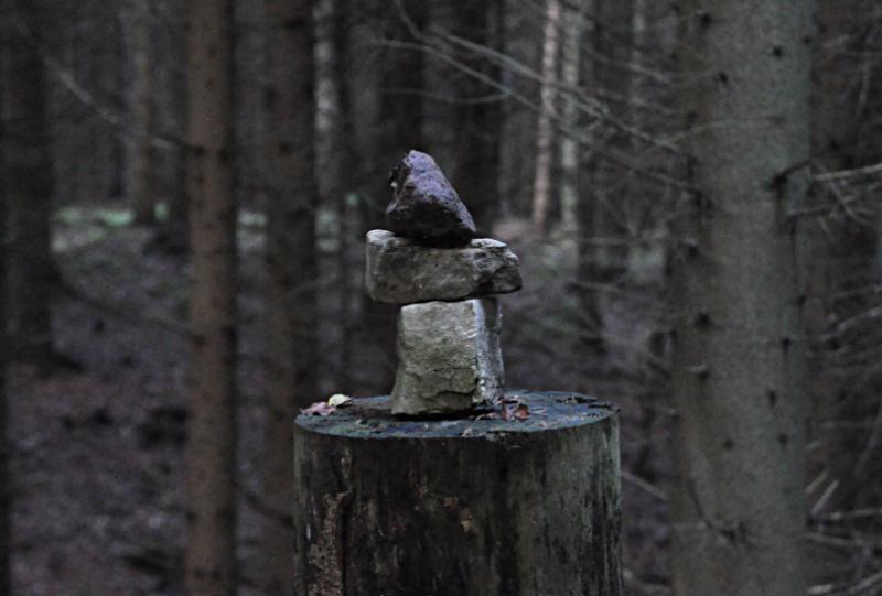 Drei Steine auf einem Baumstumpf gestapelt
