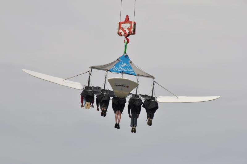 Fünf Personen hängen an einem von einem Kran hochgezogenen Flieger.