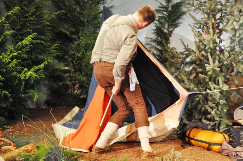 Ein Mann versucht ein Zelt aufzubauen.
