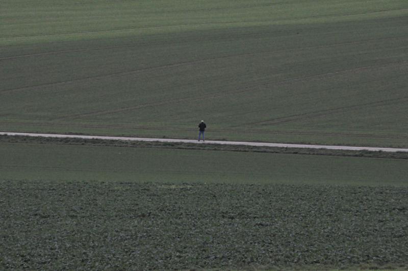 Ein Mann geht auf einem Feldweg