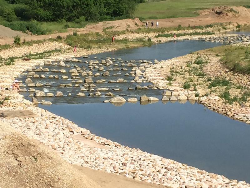 Ein Fluß wird an einer Passage mit großen Steinen ausgebremst