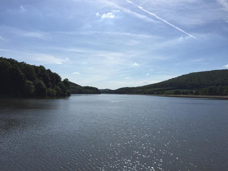 Ein See, rechts und links bewaldete Hügel.