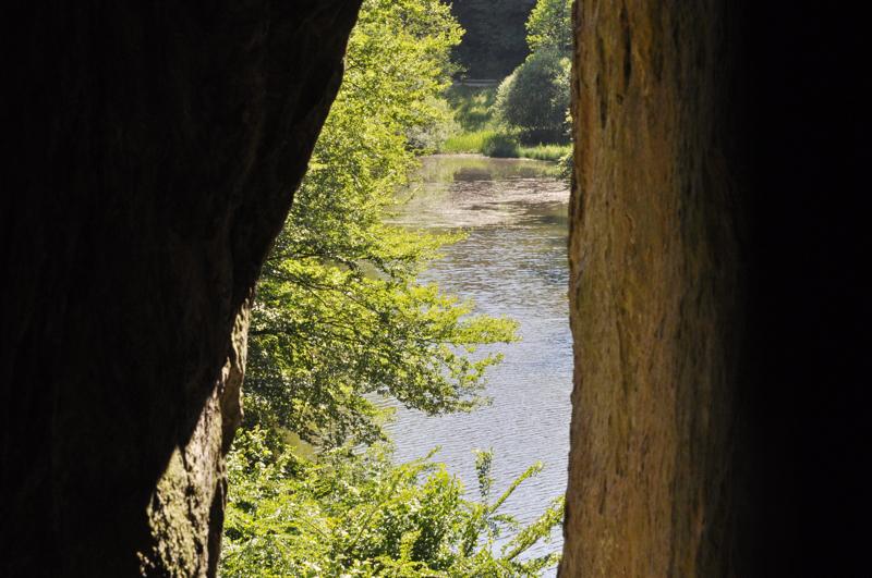 Blick durch eine Felsspalte auf einen See.