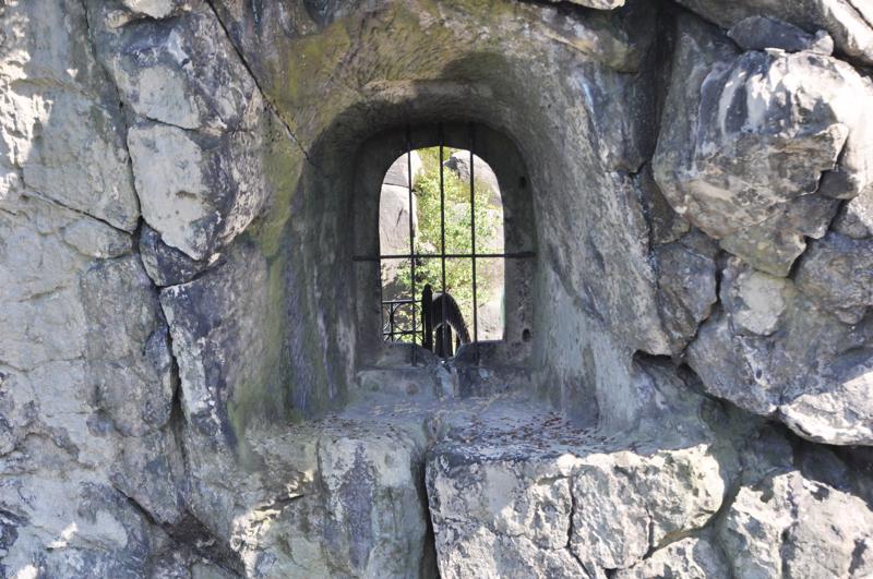 Blick auf ein in Fels gehauenes, vergittertes Fenster