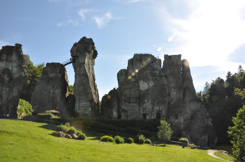 Felsen in Stelenform ragen aus einem grünen Hügel.