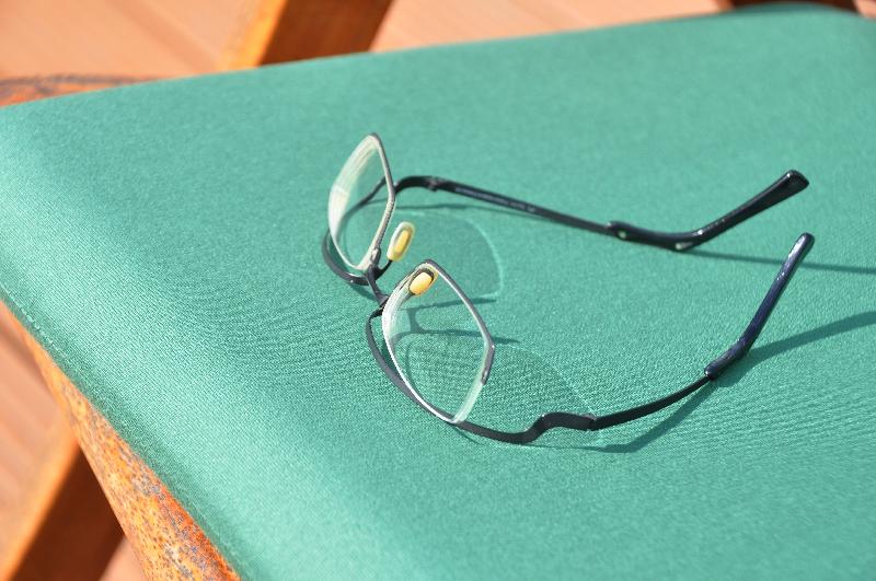 Eine Brille liegt auf einem Balkonstuhl
