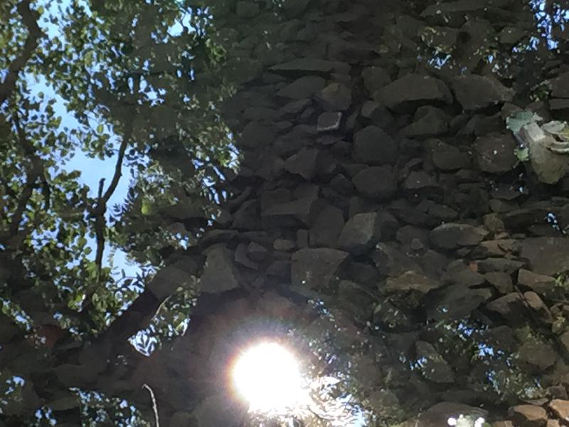 Ein Steinturm in dem sich die Sonne spiegelt