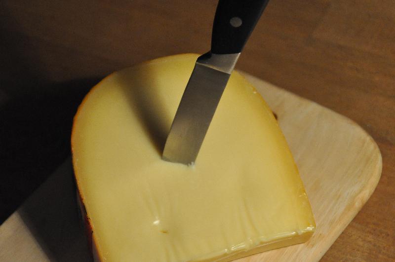 Ein Stück Käse, in dem ein Messer steckt