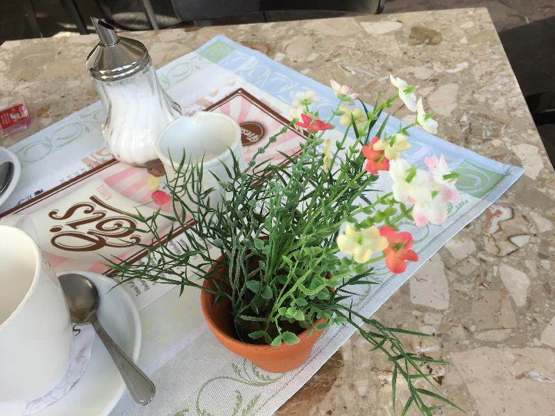 Pflastikblumen an Kaffeetasse