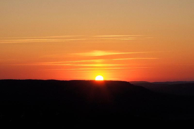 Die Sonne geht hinter Hügeln unter